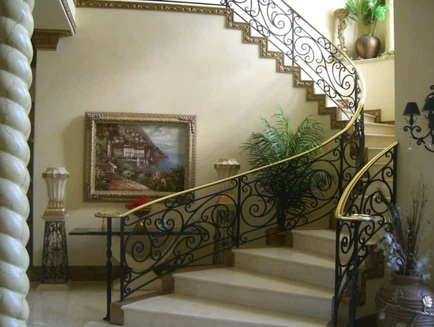 A staircase with white tiles flooring and black railings, along with gold-finished handrails.