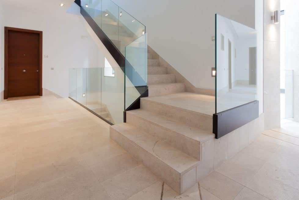 This house features a staircase with marble tiles flooring and glass railings.