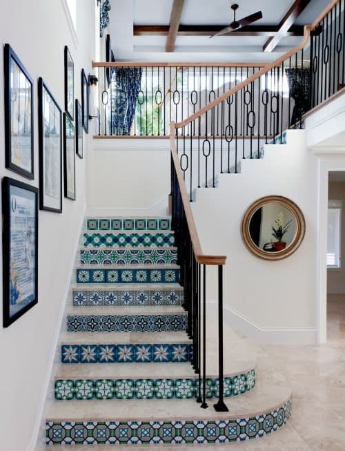 This staircase features charming flooring and white walls, along with iron railings.
