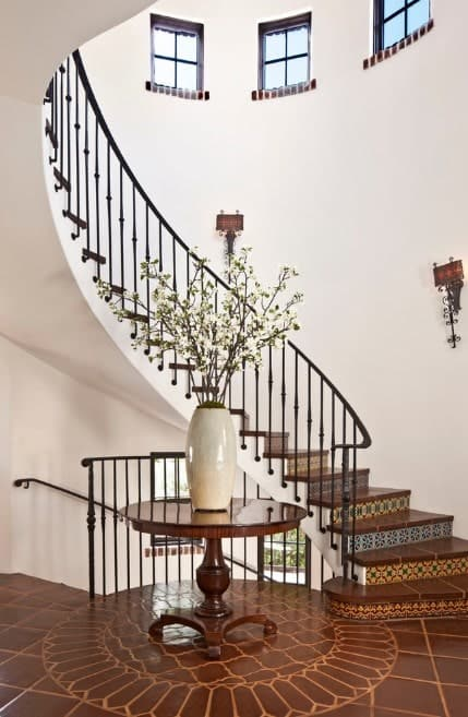A gorgeous curved staircase with brown tiles flooring surrounded by white walls and lighted by wall lighting.