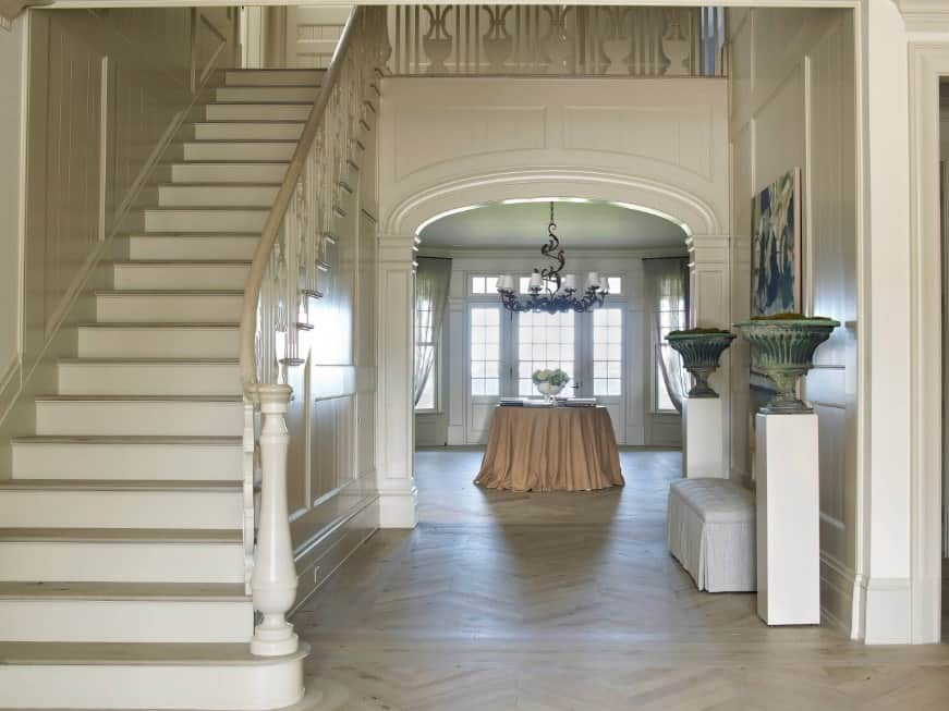 This home boasts an entry with a glamorous chandelier and a centerpiece table. The classy staircase with white railings leads to the home's second floor.