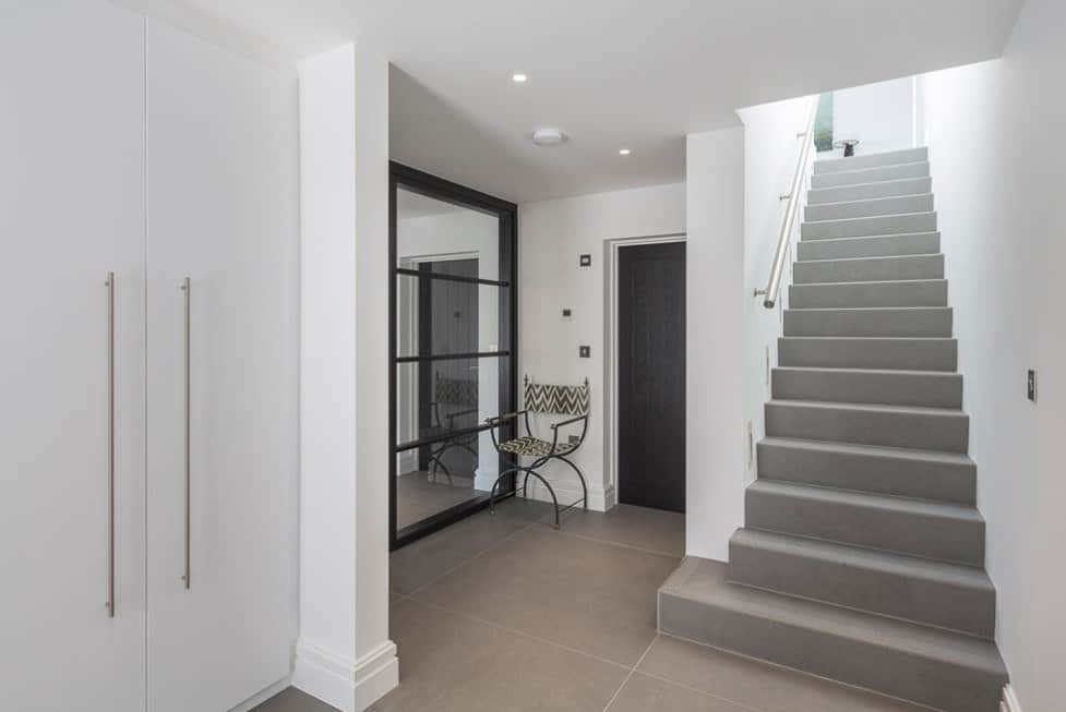 A straight staircase with gray flooring and white walls.