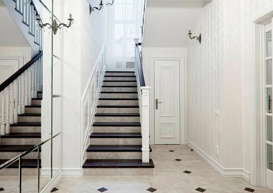 This home boasts a staircase with dark brown floors and white railings, lighted by elegant wall lights.