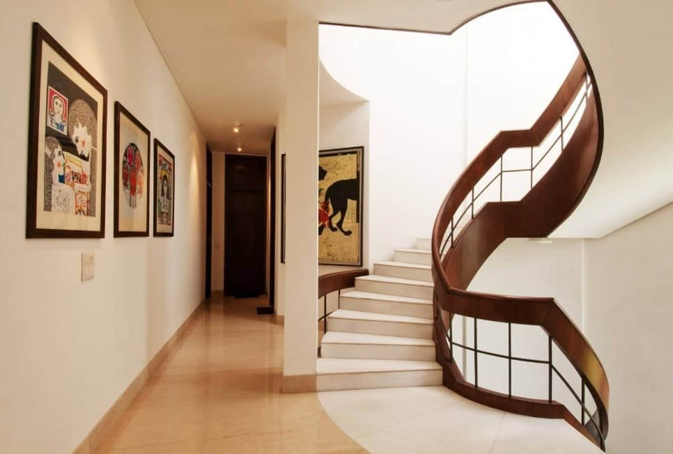A circular staircase with handsome brown railings and white tiles flooring matching the white walls.