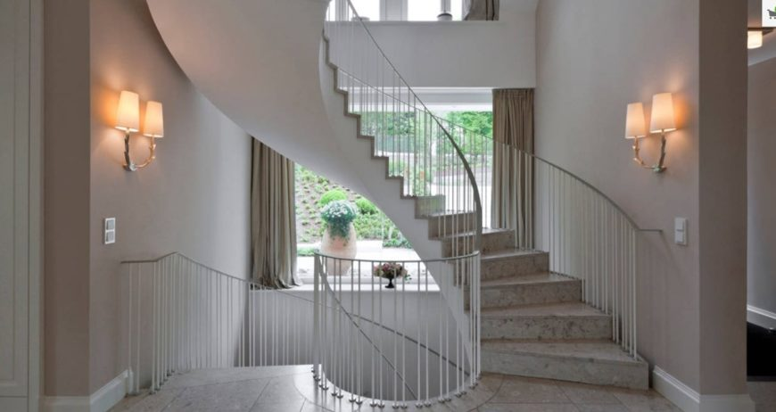 A circular staircase featuring marble tiles flooring and thin white railings lighted by wall lights.