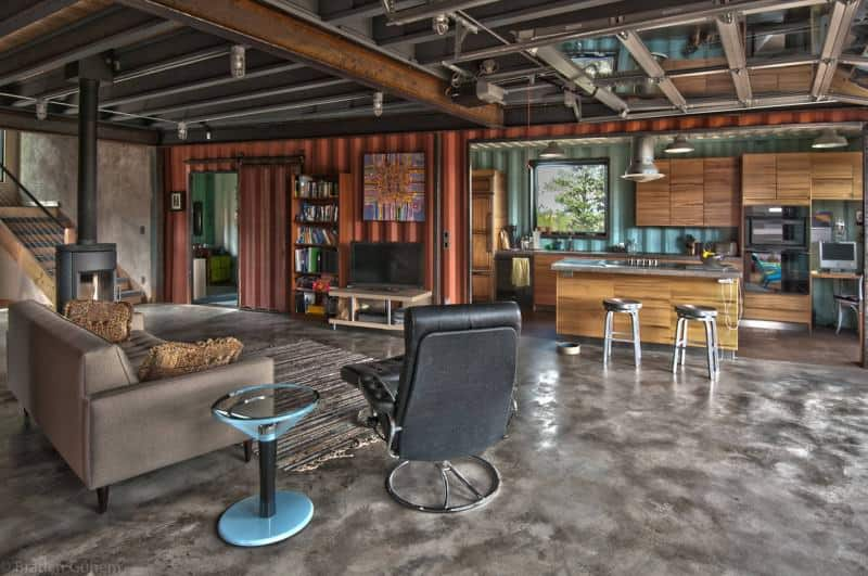 Open concept living space in side a small container house with living room and kitchen. Done in an industrial-style.