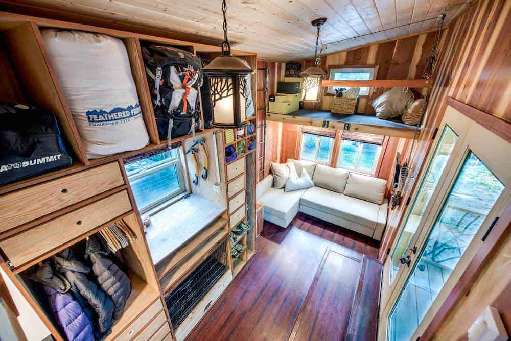 Spectacular tiny house interior photo with living room, sleeping loft and kitchen area.
