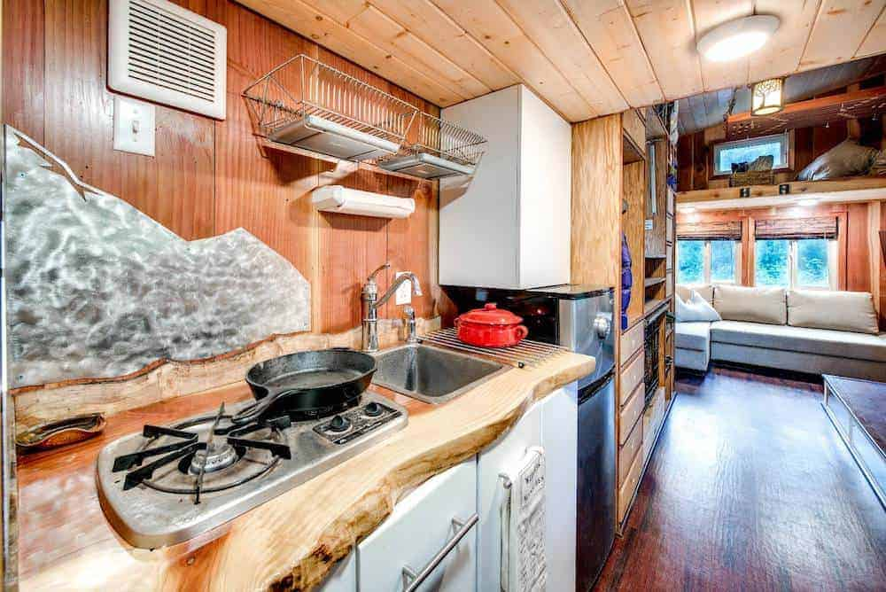Close-up photo of a tiny home kitchen with custom woodwork, sink, cabinets, backsplash and range.
