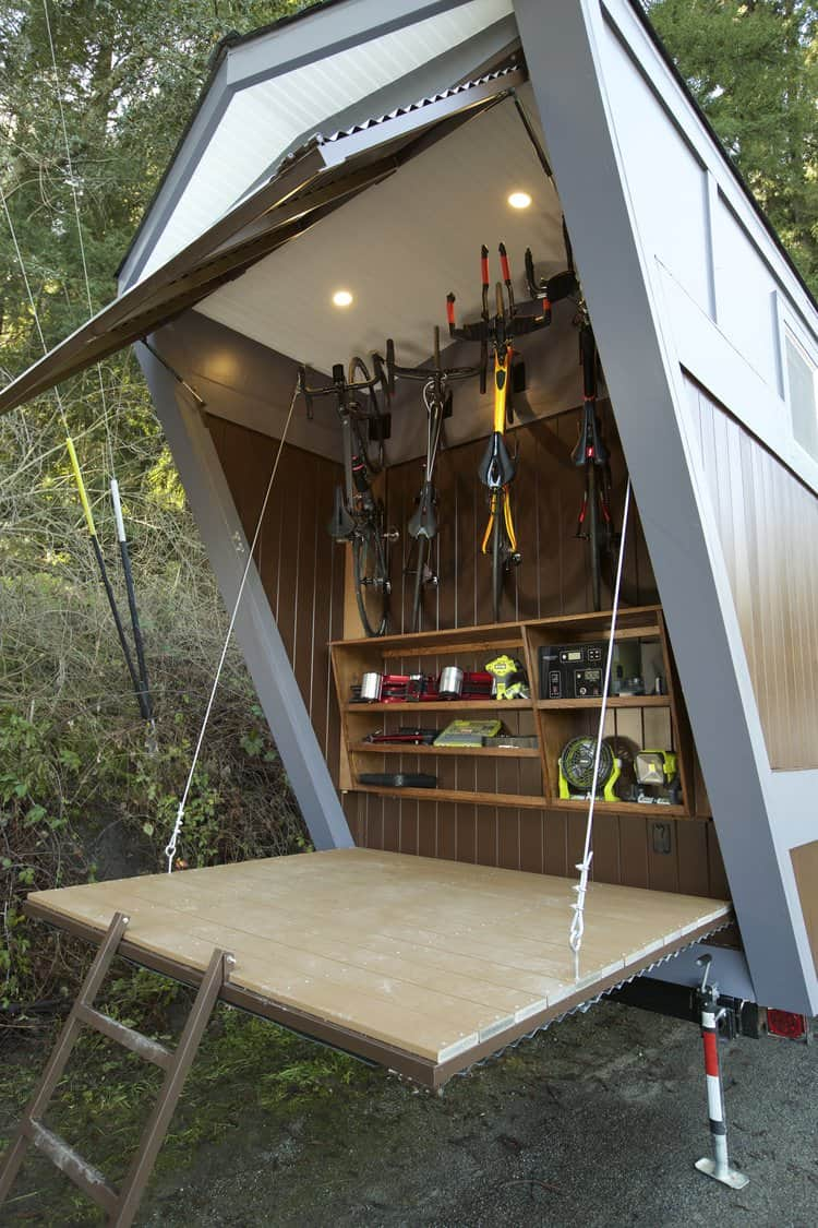 Tiny house with bicycle storage garage accessible with drop-down door on one end.