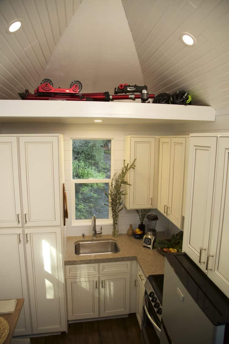 Tiny house kitchen with plenty of storage including a small pantry.