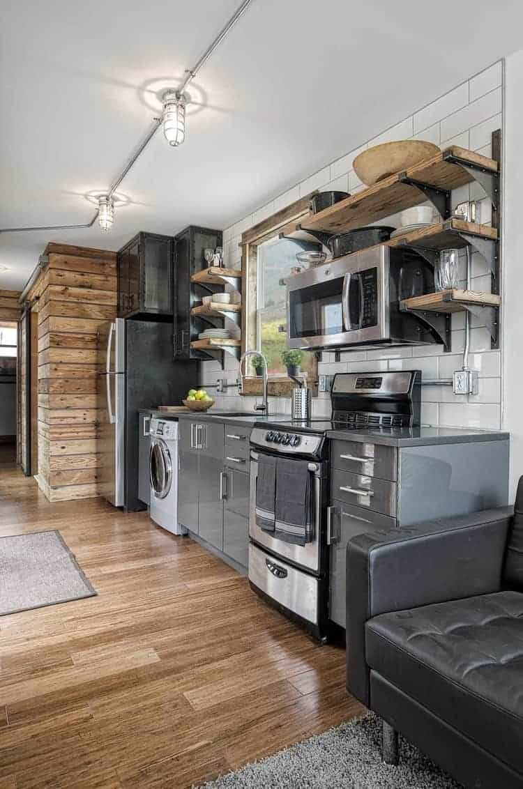 Long single wall tiny house kitchen with white tile backsplash to the ceiling. The modern cabinets are in gray with stainless steel appliances. The fridge is large for a tiny home. Open-faced shelving offers additional storage above the cabinets. One other notable touch is the large picture window above the sink which brings in plenty of light into the kitchen area and the main living space.