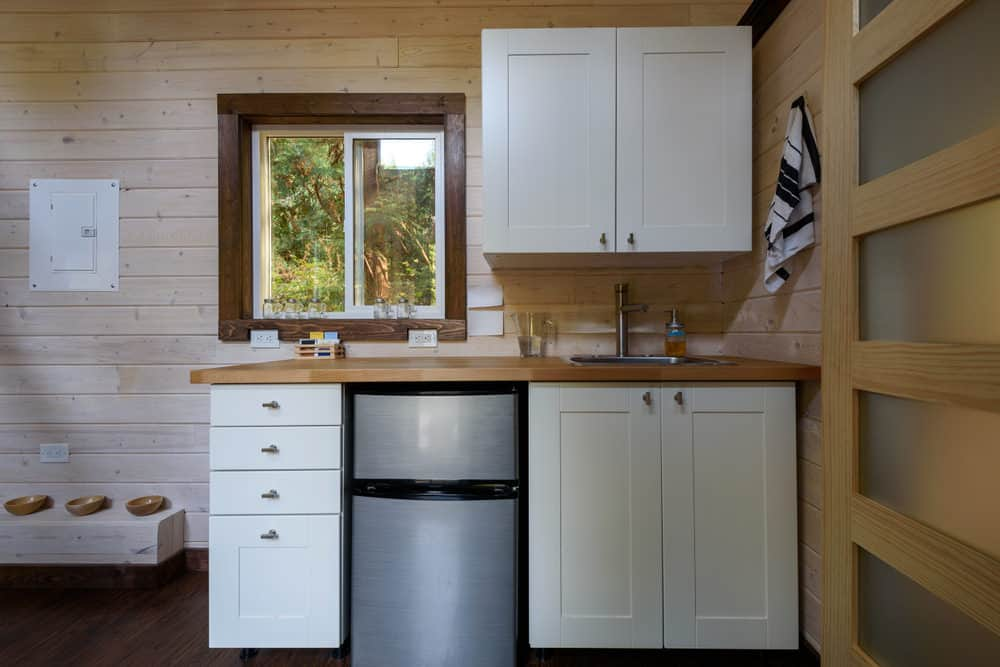 Here's an example of a very small kitchen in a small tiny house. The fridge is tiny but fits well in the small cabinet area.
