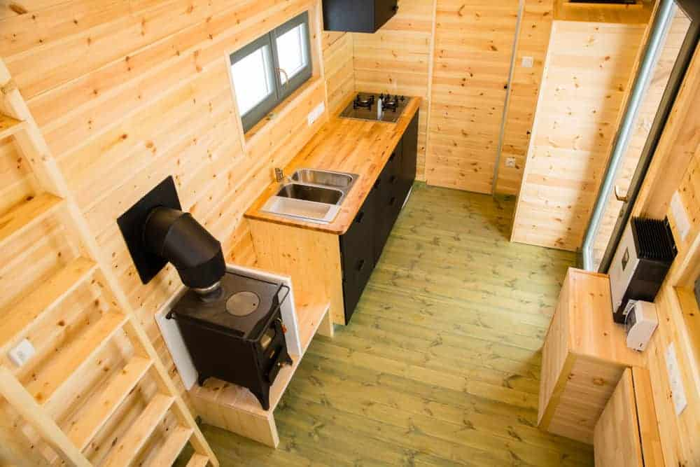 This is a minimalist tiny house with all the open space. The kitchen is a simple affair with a double sink and range.