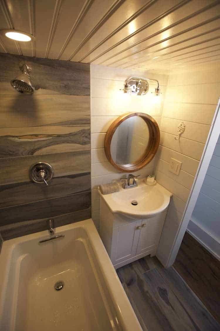 Tiny house vanity and sink with round wood-framed mirror next to large tub/shower combo.