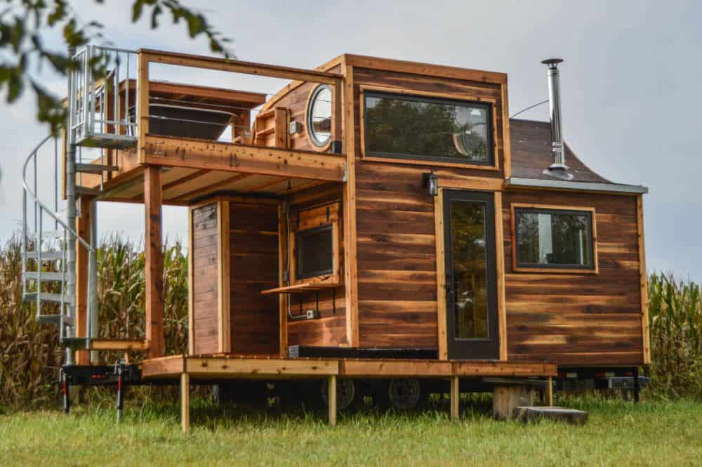 Tiny house with covered lower deck and roof-top deck accessible by cool spiral staircase.