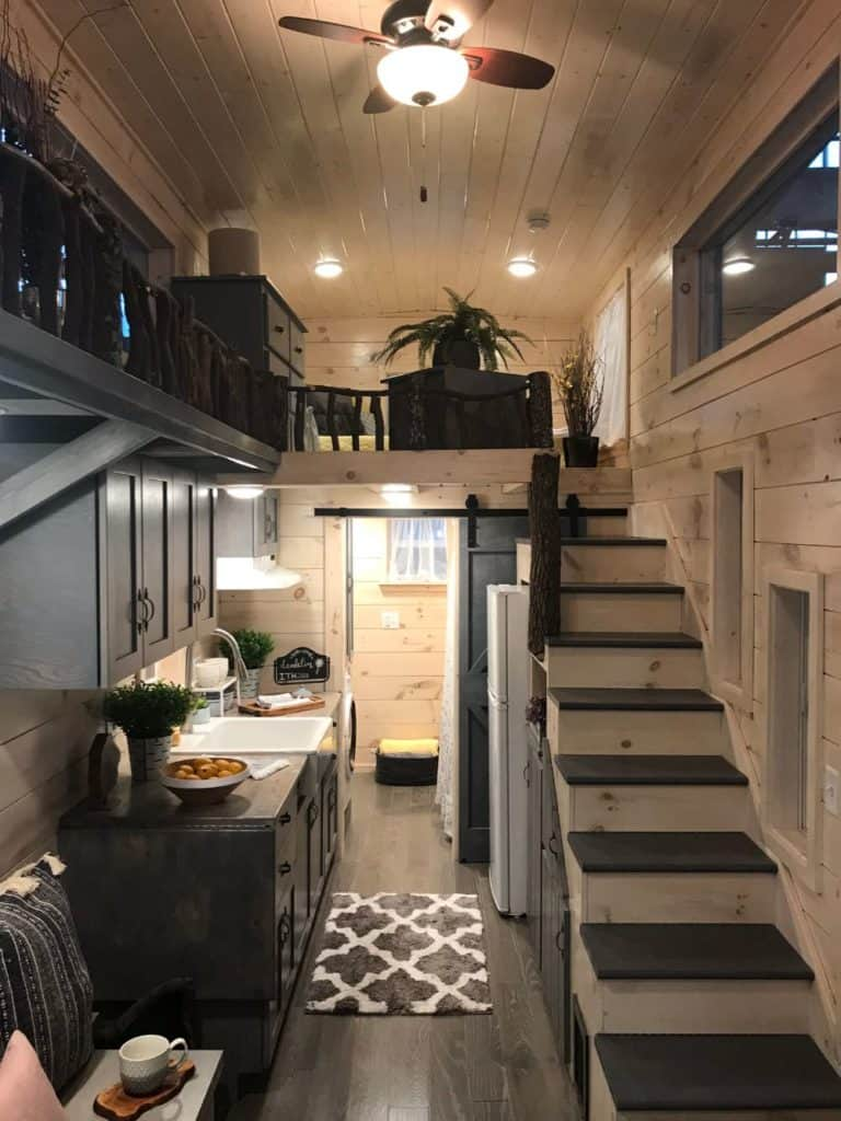 This wooden staircase doubles as storage and it leads to the bedroom loft with a pet walk bridge that connects to the pet loft. It has a trunk that accents and adds warmth in the house.