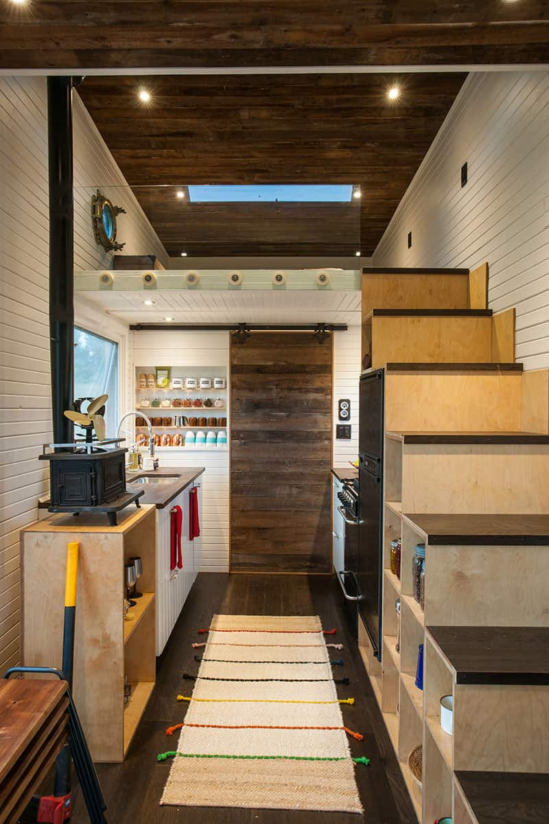 This one's a smart kitchen setup. The staircase serves as shelves where you can put jars or containers and a fridge too.