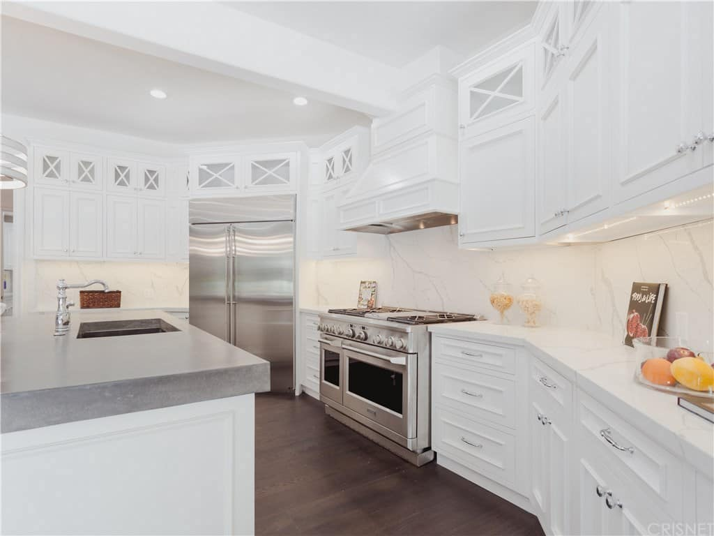 This brilliantly white kitchen has a dark hardwood flooring that contrasts the white brightness of the shaker cabinets and drawers of the peninsula. This is complemented by the modern appliances and the kitchen island countertop.