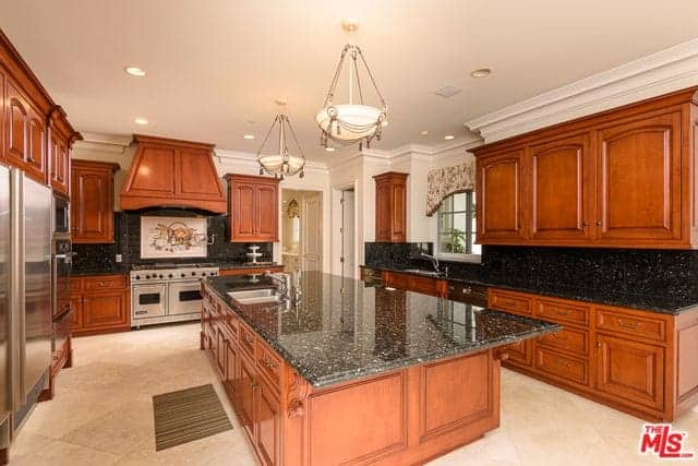 The black countertops and backsplash are perfectly paired with wooden cabinetry that has a traditional design to it that stands out against the beige floor tiles and beige ceiling.