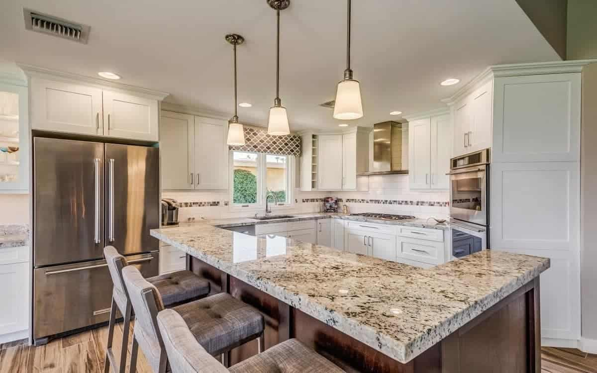 The L-shaped kitchen island and peninsula has gray marble countertops that perfectly match the modern appliances, backsplash and the trio of cushioned stools by the kitchen island.