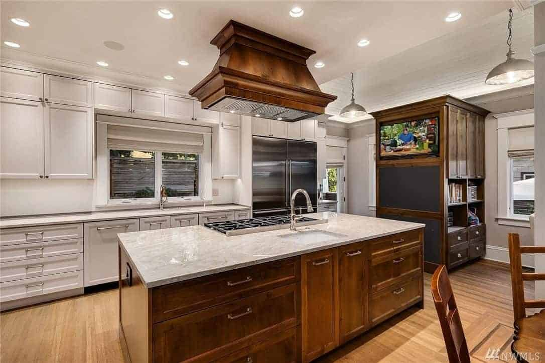 The kitchen island is made of wooden elements that reflect the vent hood of the cooking area and the structure that houses the TV. They all match with the hardwood flooring and is given a nice background of a white peninsula and white ceiling.