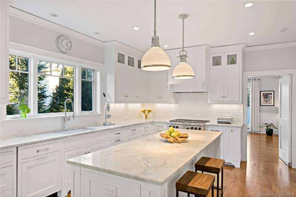 A pair of dome-shaped pendant lights provide a dash of elegance and warm light to the white marble countertops of the kitchen island and L-shaped peninsula that contrasts the hardwood flooring.