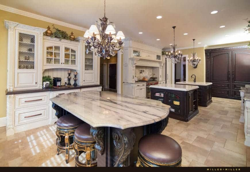 This large marble-floored kitchen has enough space for three kitchen islands that has white marble countertops over dark wood cabinetry. Each of the kitchen islands is topped with an elegant wrought iron chandelier.