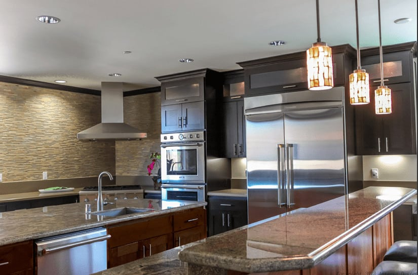 The textured and patterned beige walls are paired with beige countertops of the peninsula and two kitchen islands. These are contrasted by silvery metallic appliances  supported by chocolate brown cabinetry.