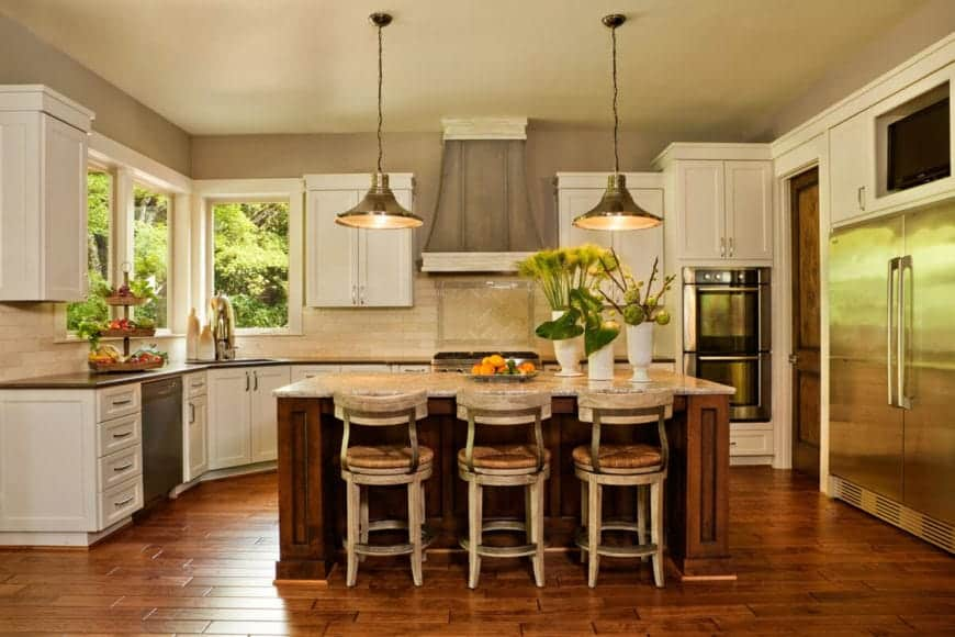 The trio of rustic distressed stools are a perfect pairing for the wooden kitchen island that blends with the wood-like tiles of the floor. The curved kitchen island has black countertops that contrast the beige backsplash.