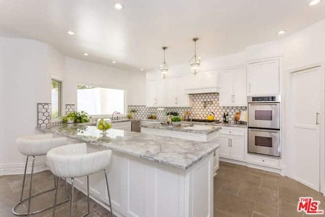 This lovely kitchen has a U-shaped peninsula that has gray marble countertops that contrast the white shaker cabinets. The patterned tiles of the backsplash adds a dash of color to the white brightness of this kitchen.