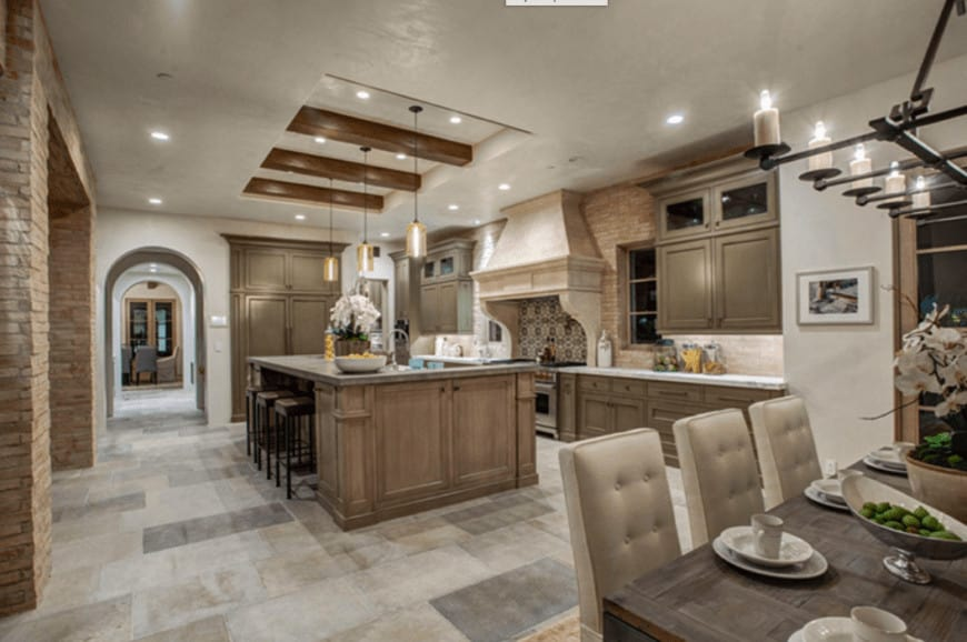 The white tray ceiling has exposed wooden beams in the middle of the tray. This matches the wooden kitchen island and peninsula that has white countertops and beige backsplash that matches the beige vent hood over the cooking area.