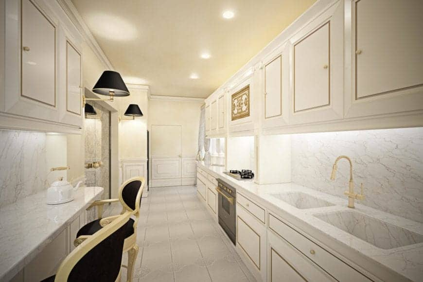 This hallway-like kitchen has white cabinets and drawers that are trimmed with golden elements that match the golden faucet over a modern sink. The white brightness is contrasted by a few black details from the wall-mounted lamps and armchairs.