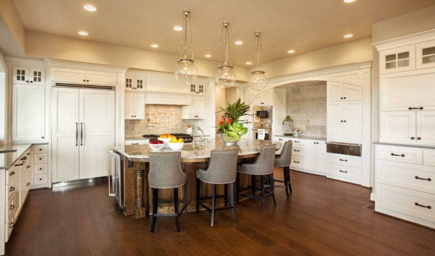 The large kitchen island that blends with the hardwood flooring is paired with four gray cushioned stools that stand out against the white shaker cabinets and drawers that dominate the beige walls.
