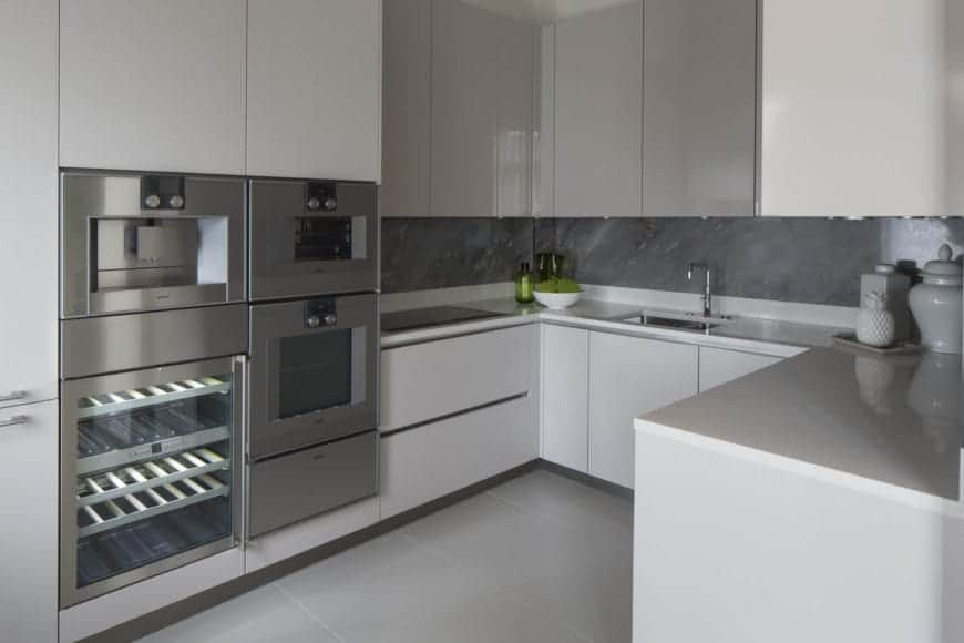 The white handle-less cabinets and drawers of the U-shaped peninsula is a nice background for the gray countertop and backsplash as well as the modern metallic appliances housed in the peninsula structure.