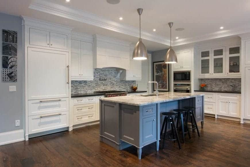 The black stools stand out against the light gray kitchen island that matches the patterned backsplash of the L-shaped peninsula. The hardwood flooring is a nice contrast for the white tray ceiling with a pair of silver pendant lights.
