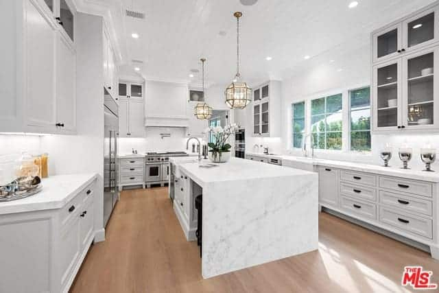 This kitchen has brilliant white marble countertops for its kitchen island and peninsula that matches the white ceiling and white cabinetry. This makes the pendant lights stand out spherical brass design.