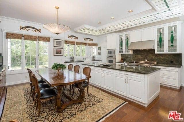 This kitchen shares the space with the dining area. The kitchen has a white ceiling with light panels that has a green pattern that is contrasted by the dark gray backsplash and countertops that stand out against the white cabinetry.
