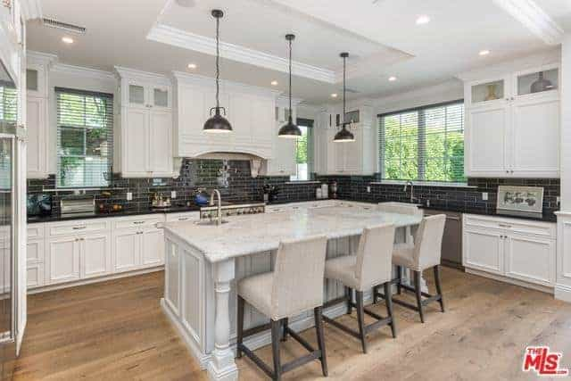 The white tray ceiling is a perfect match for the shaker design of the cabinets and drawers of the kitchen island and L-shaped peninsula that is contrasted by a black countertop and black brick-like backsplash.