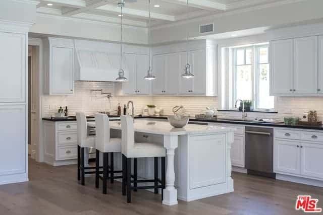 The white kitchen island with a white countertop is paired with white stools that has wooden legs blending with the hardwood flooring. The white shaker cabinetry of the L-shaped peninsula is a match for the white coffered ceiling.