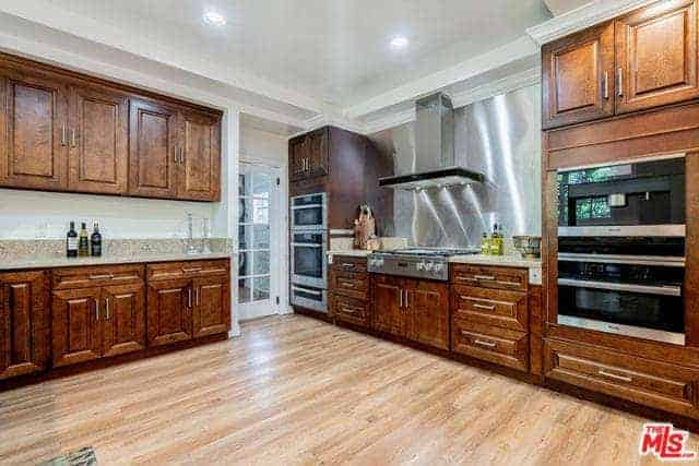 This kitchen has a wide floor space with the absence of a kitchen island on its hardwood flooring. The walls are dominated by wooden cabinetry that houses modern appliances paired with a white tray ceiling.