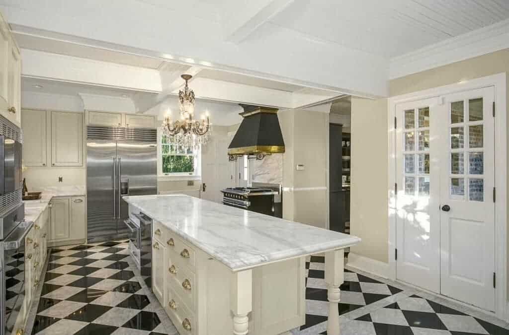 The highlight of this white kitchen is the black and white checkered flooring. This black and white aesthetic is extended to the rest of the kitchen with white cabinetry and black cooking area with a black vent hood against the white coffered ceiling.