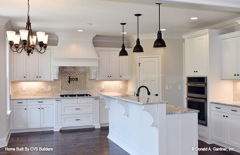 The white cabinets and island of this kitchen are beautifully contrasted by wrought iron hardware and lighting along with dark hardwood flooring.