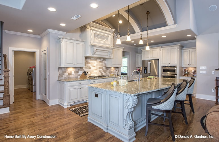 The barrel-vaulted ceiling lined with decorative white trims creates a striking character to this traditional kitchen.