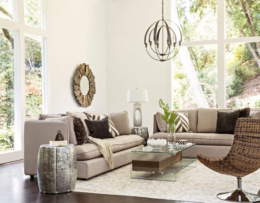 This Transitional-style living room is made of different textures and tone all coming together with the brightness of the tall white walls and windows that bring in natural lights. This goes well with the gray sofas, silver end tables and glass coffee table.