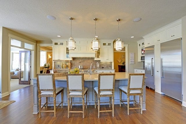 This charming kitchen has beige cabinetry, stainless steel appliances, and a center island bar lined with cushioned counter chairs and topped with glass pendant lights.