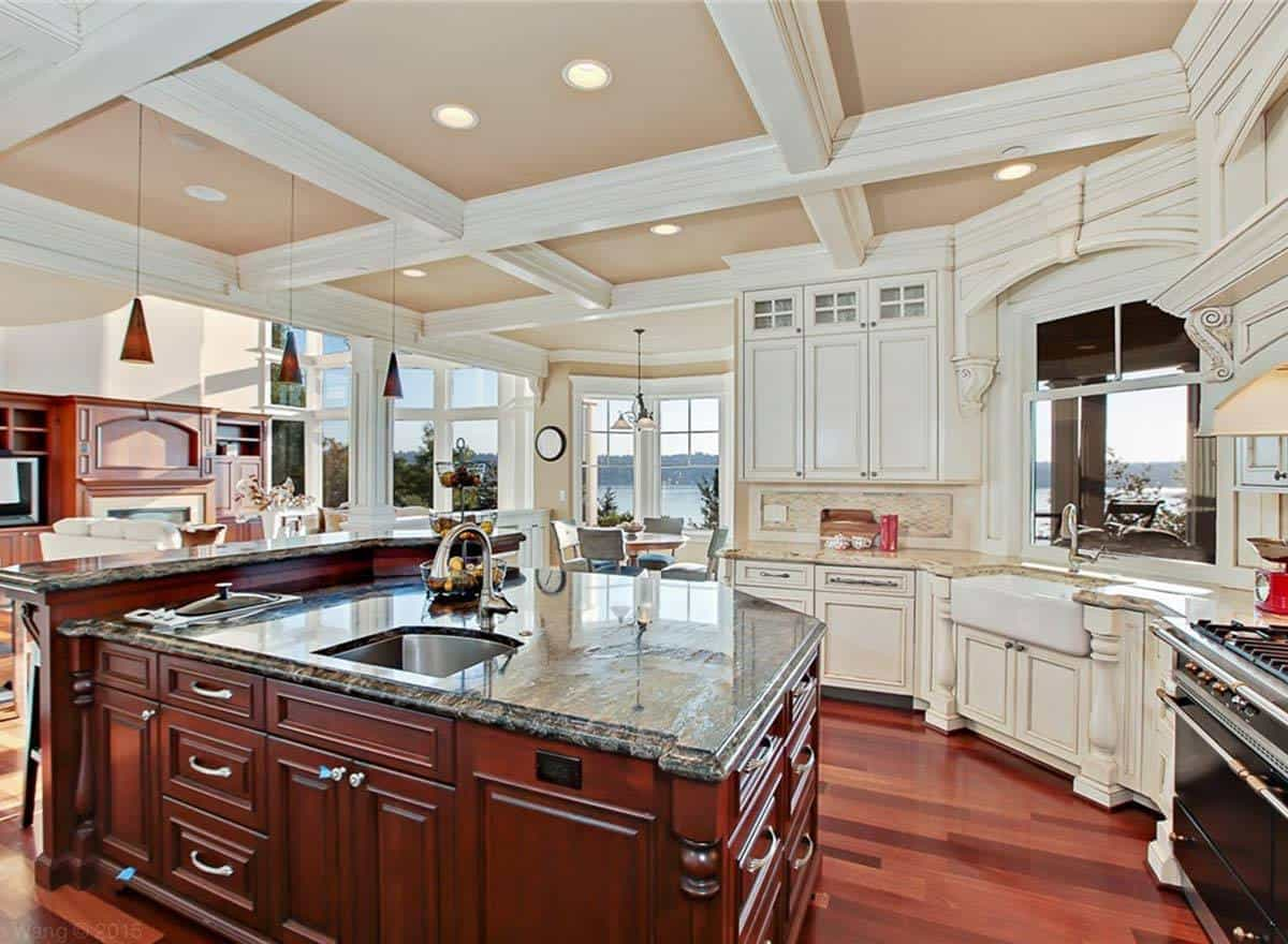 This kitchen has a gorgeous coffered ceiling and rich hardwood flooring that matches the granite-top L-shaped island counter.