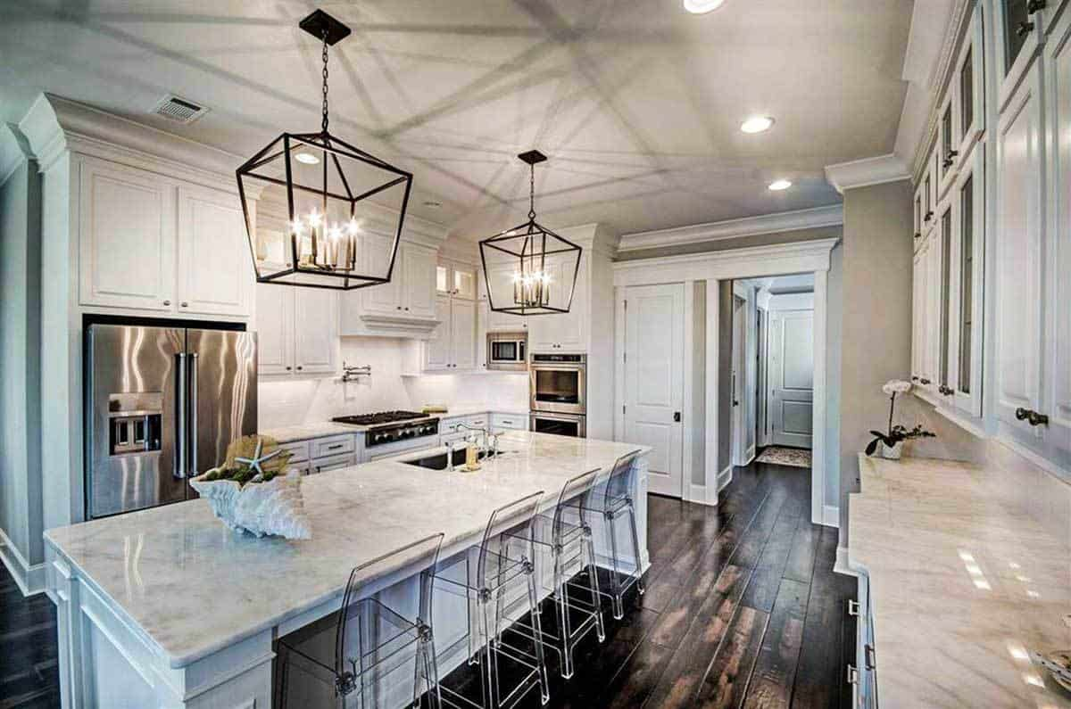 This charming kitchen showcases its white cabinetry, stainless steel appliances, and marble top center island complemented with glass counter chairs and a pair of caged pendants. These are all complemented by the charming hardwood flooring.
