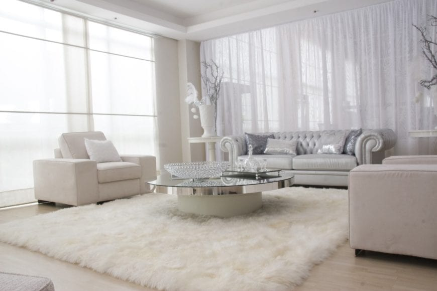 This white modern formal living room shines with a wintry beauty. It has a silver sofa paired with a white furry area rug that looks like snow. This is topped with a glass-top coffee table that is adorned with various glass decors that is brightened by the natural lights coming in from the bright windows.
