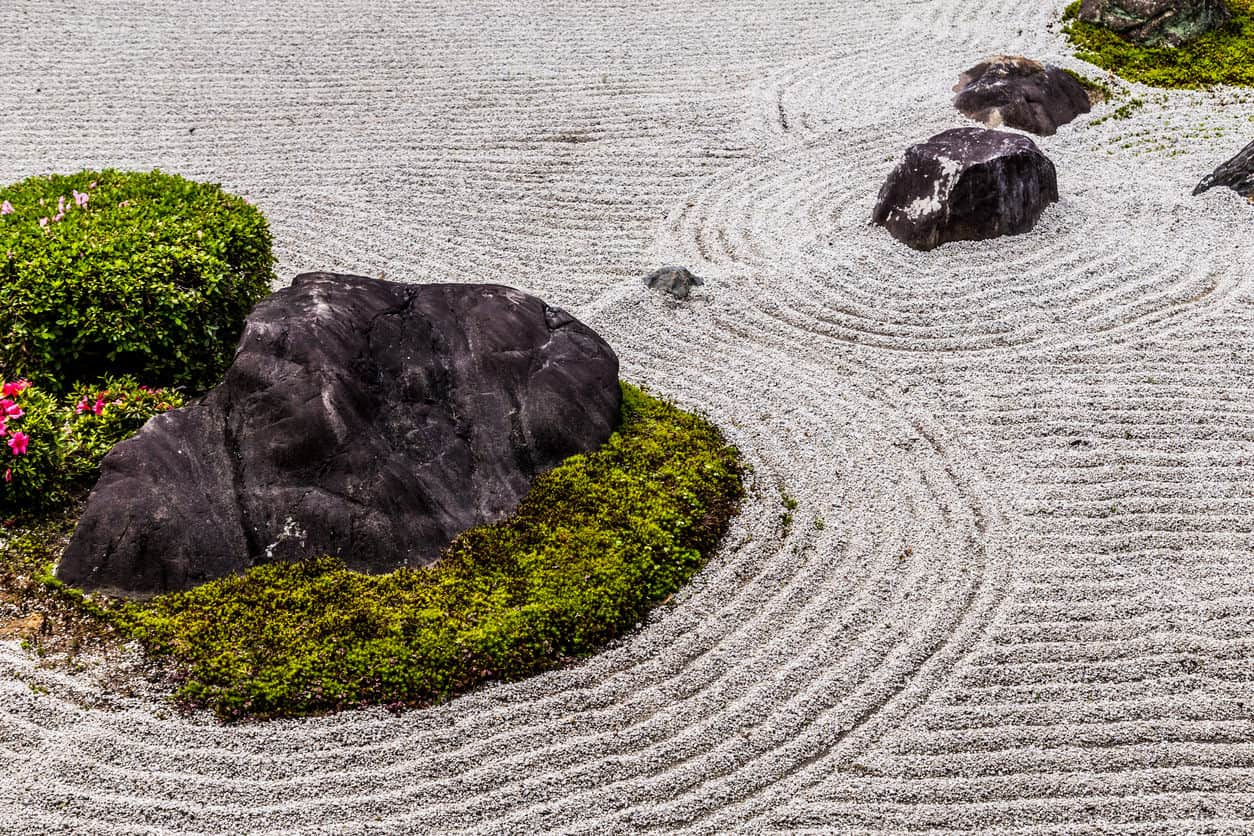 "The Japanese rock garden Karesansui) or ""dry landscape"" garden, often called a zen garden, creates a miniature stylized landscape through carefully composed arrangements of rocks, water features, moss, pruned trees and bushes, and uses gravel or sand that is raked to represent ripples in water."
