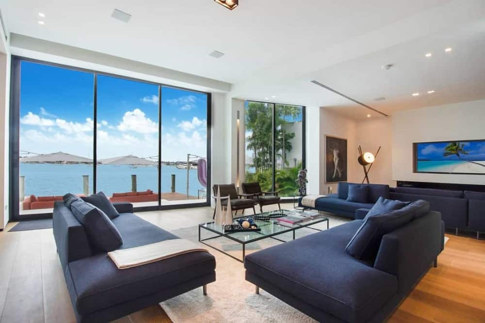 This is a close look at the living room that has dark cushioned sofas surrounding a glass-top coffee table that matches with the glass walls on the opposite side with a view of the sea.
